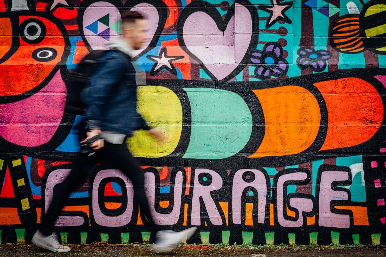 un-jeune-qui-passe-devant-un-graffiti-courage